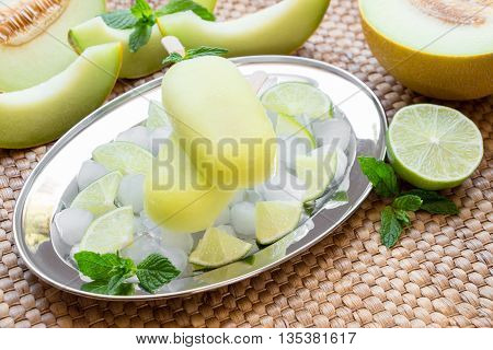 Melon and lime sorbet ice cream on silver plate with ice cubes lime pieces mint leaves near melon slices lime on a straw napkin background. Melon and lime sorbet ice cream popsicles. Horizontal.