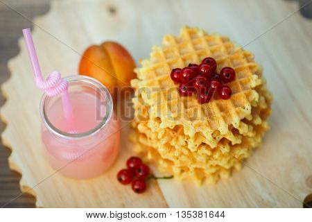 Belgian waffles with fresh berries on cutting board on background of rustic. grapefruit juice. pink cocktail with a straw.