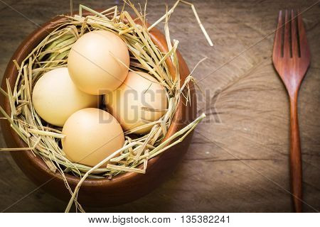 Eggs in wooden bowl with fork on wooden background