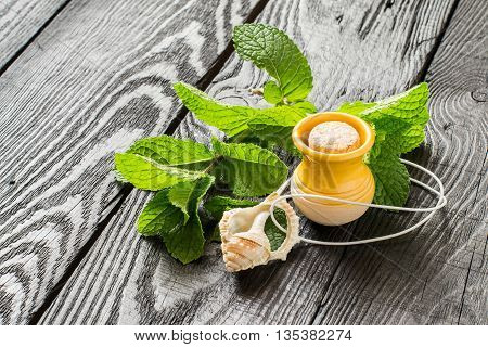 Mint essential oil in a small yellow clay jar and pendant aromatic fresh mint on a dark wooden table