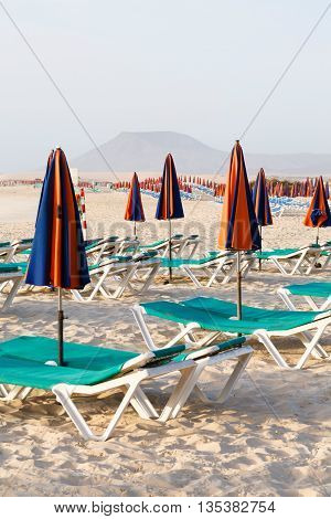 Empty sun loungers and parasols on a beach