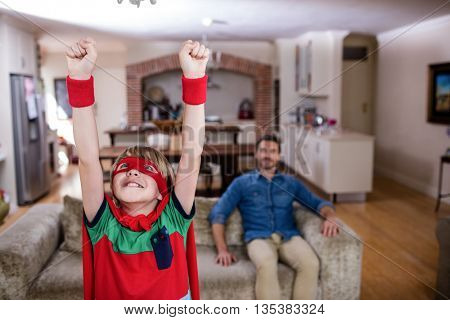 Son pretending to be a superhero while father sitting on sofa at home
