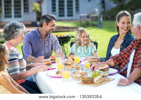 Happy multi-generation family sitting at table in back yard