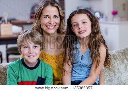 Portrait of happy mother and kids sitting on a sofa at home