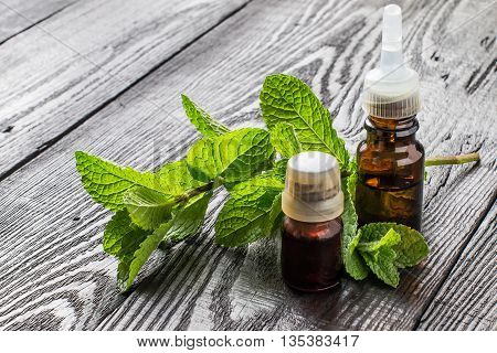 Mint essential oil in small brown bottles and fresh mint on a dark wooden table