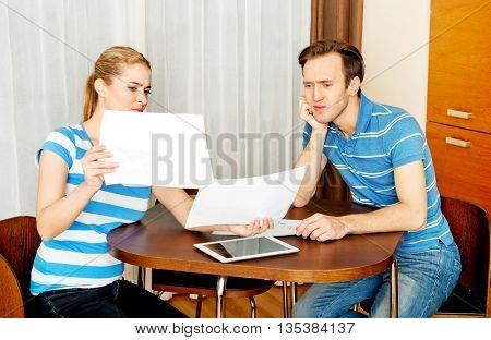 Young couple sitting at the desk and looking for plans of new house