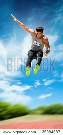 Sportsman jumping against athletics field on a sunny day