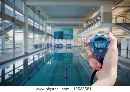 Close up of a hand holding a chronometer outside of the swimming pool