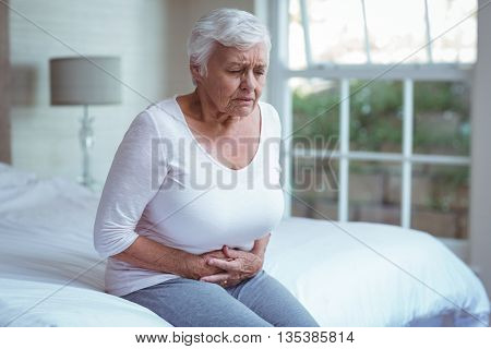 Senior woman suffering from stomach pain while sitting on bed