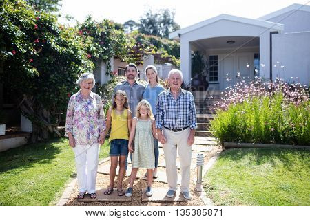 Multi-generation family standing together on the garden path