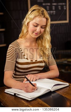 Pretty blonde woman writing on planner in coffee shop