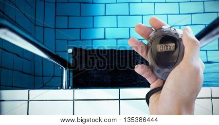 Composite image of coach is holding a stopwatch against water moving in the swimming pool