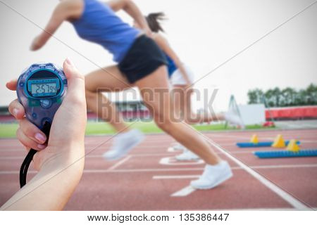 Composite image of a woman holding a chronometer to measure performance against runners starting the race