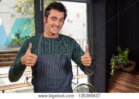 Waiter showing thumbs up in a coffee shop