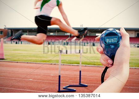 Composite image of a woman holding a chronometer to measure performance against serious male athlete jumping above hedge during a race