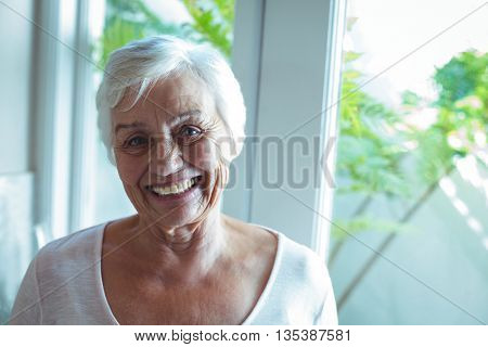 Portrait of happy senior woman against window at home