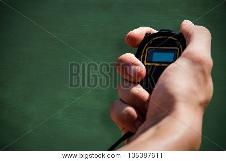 Close up of hand holding a chronometer against green chalkboard