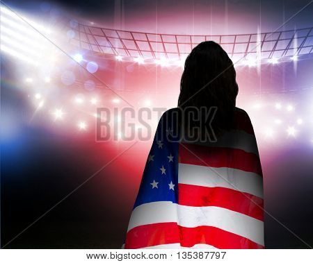 Rear view of sporty woman holding an American flag against american football arena