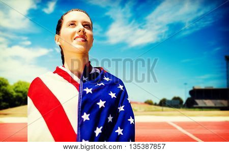 Low angle view of sporty woman holding a American flag against tracks on a sunny day