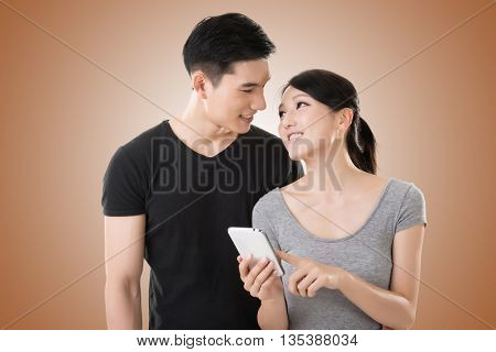 Asian young couple using cellphone, closeup portrait.
