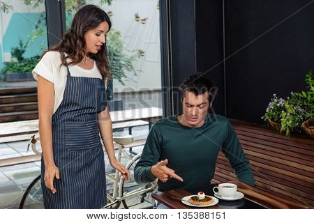 Angry client quarreling with waitress about wrong order in coffee shop