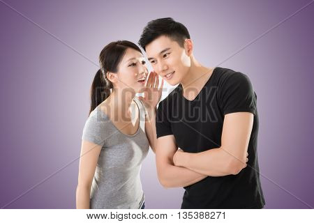 young Asian couple whisper, closeup portrait.