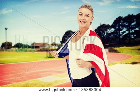 Female athlete with american flag on her shoulders against athletics field on a sunny day