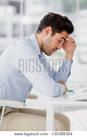 Frustrated businessman sitting on desk with hand on head in office