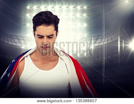 Athlete with american flag wrapped around his body against american football arena