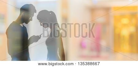 Couple using cellphone, silhouette portrait.