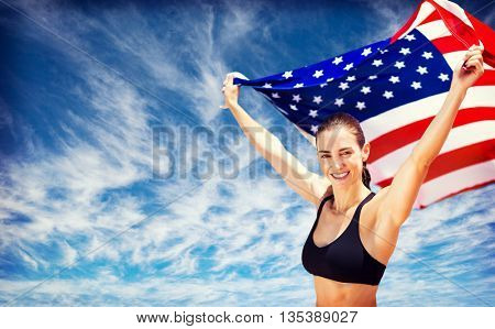 Portrait of happy sportswoman raising an american flag against view of the blue sky