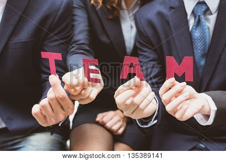 Business team holding a text paper of team.