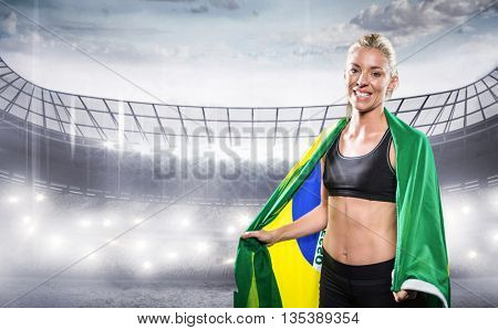 Athlete with brazilian flag wrapped around his body against sports arena