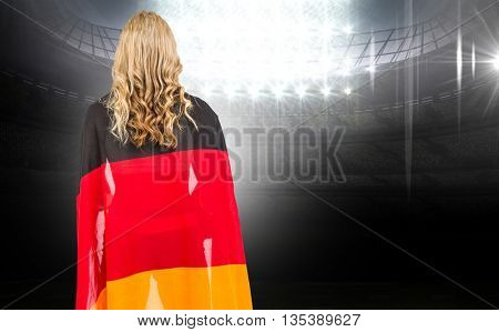 Athlete with german flag wrapped around his body against american football arena