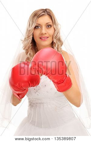 Vertical shot of a cheerful bride with red boxing gloves isolated on white background