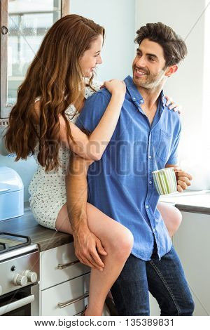 Young couple embracing in kitchen while having coffee at home