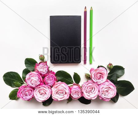 Colorful composition with sketchbook roses and pencils. Flat lay on white table top view