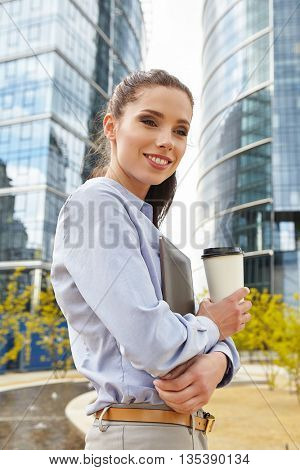 Beautiful young businesswoman with a disposable coffee cup, drinking coffee, and holding tablet in her hands against city office.