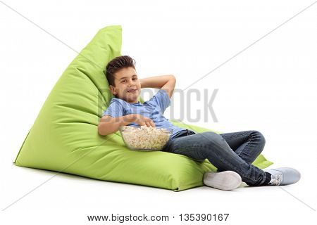 Joyful kid sitting on a comfortable green beanbag and eating popcorn isolated on white background