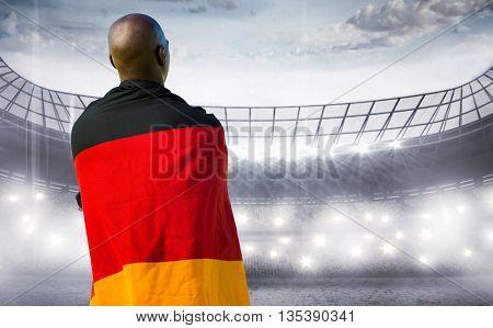 Man wearing German flag against sports arena