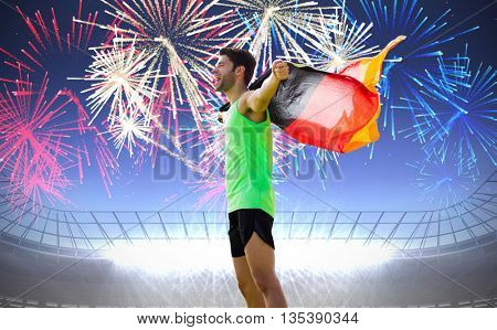 Man holding German flag against fireworks exploding over football stadium