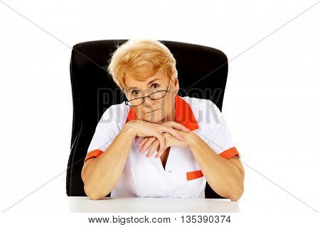 Worried elderly female doctor or nurse sitting behind the desk
