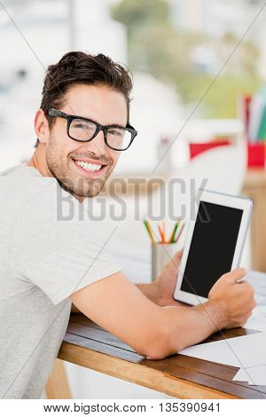 Young man using digital tablet at his desk in the offic