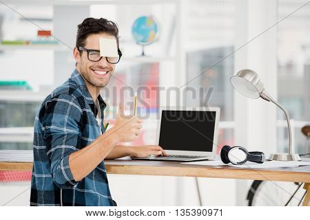 Portrait of young man showing thumbs up while working at his desk in the office