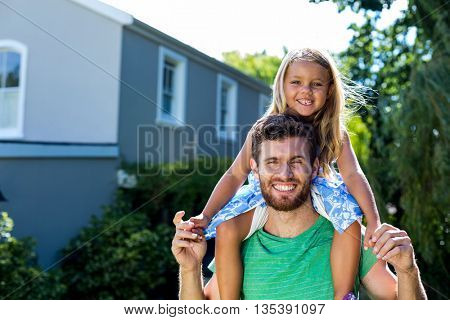 Happy father carrying daughter on shoulders in yard against sky