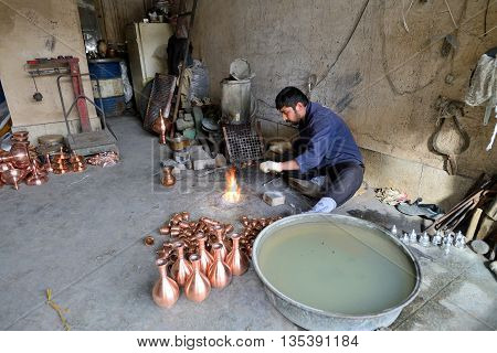 ISFAHAN - APRIL 18: Unknown man making traditional iranian souvenirs in a market (Isfahan Bazaar) in Isfahan Iran on April 18 2015. Bazaar is the most important tourist attraction in Isfahan Iran.