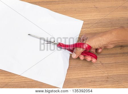 Scissors cut paper, women hand is cutting paper with scissors on a wooden table.