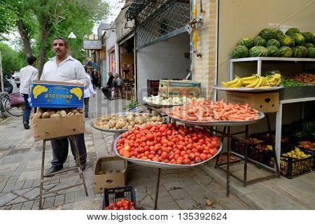 YAZD - APRIL 16: Unknown people trades fresh vegetables and fruits in street market in Yazd Iran on April 16 2015. Yazd is the capital of Yazd Province Iran and a centre of Zoroastrian culture.