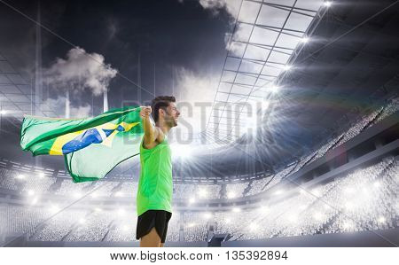 Profile view of Brazilian sportsman is holding a flag against sports arena