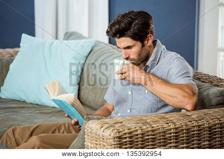 Young man having coffee while reading book in living room